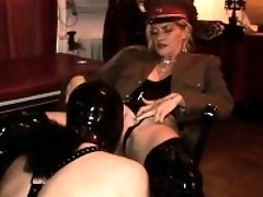 Kinky mistress puts a plug in her male slaves ass